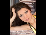 Nikita bulgaria is sited on a sofa, legs appart and looking at you
